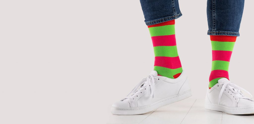 close up of person wearing pink and green striped socks