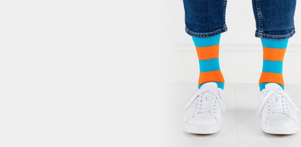 close up person wearing orange and blue striped socks