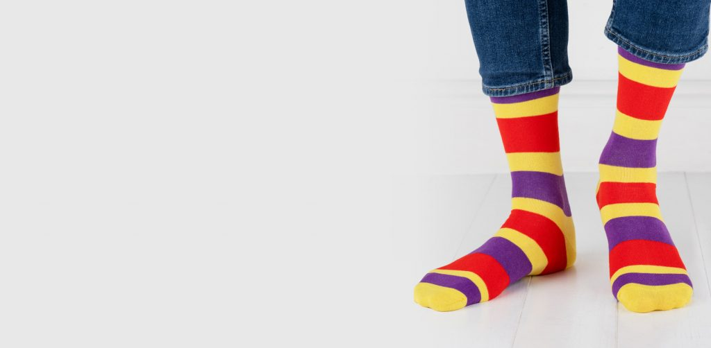 close up of person wearing yellow, purple and red socks