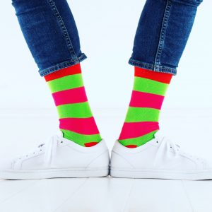 close up of person wearing pink and green patterned socks