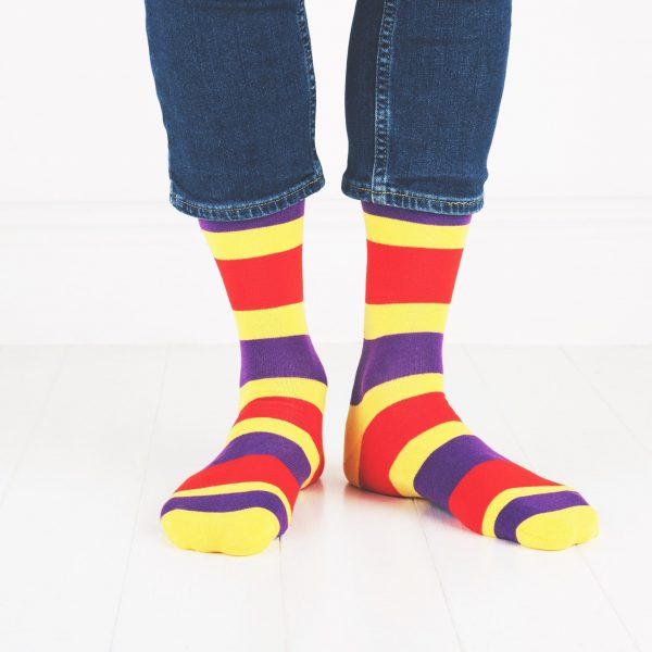 close up of person wearing yellow, red and purple socks