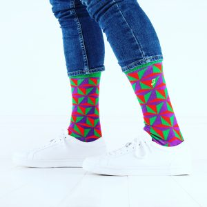 close up of person wearing green red and purple patterned socks