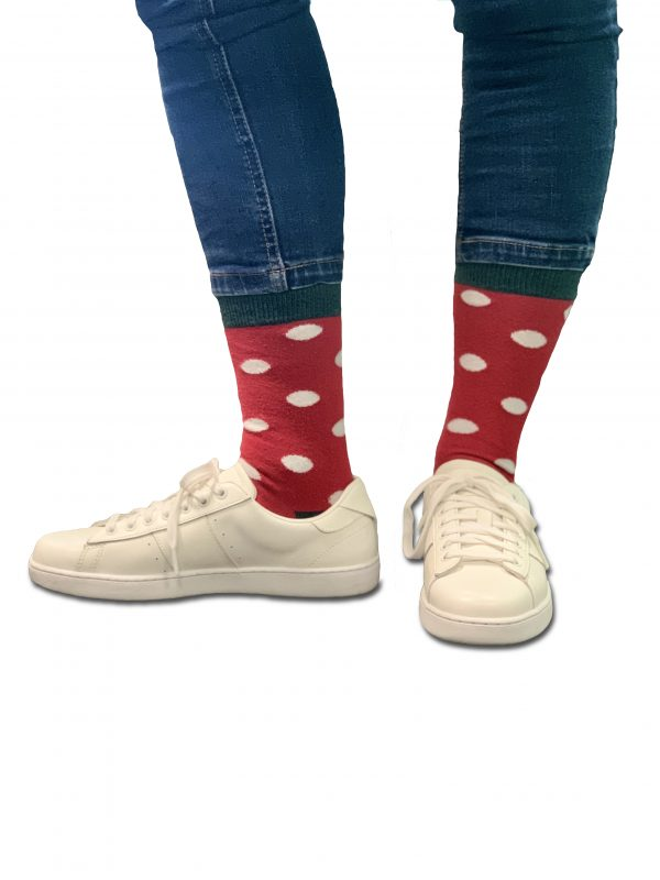 close up of person wearing red socks with white spots